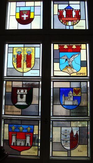 Glasmosaik på rådhuset, med venskabsbyernes byvåben